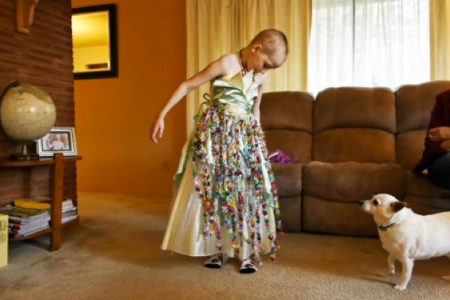 Mykayla admires her dress while her dog, Chase, looks on November 2, 2012. The dress, made for her by a family friend, contains 1,000 folded origami paper cranes. The crane folding holds cultural significance in Japan, where the gesture of folding and offering that many cranes to someone symbolizes prayers or well wishes to the recipient. (Beth Nakamura / The Oregonian / Landov)